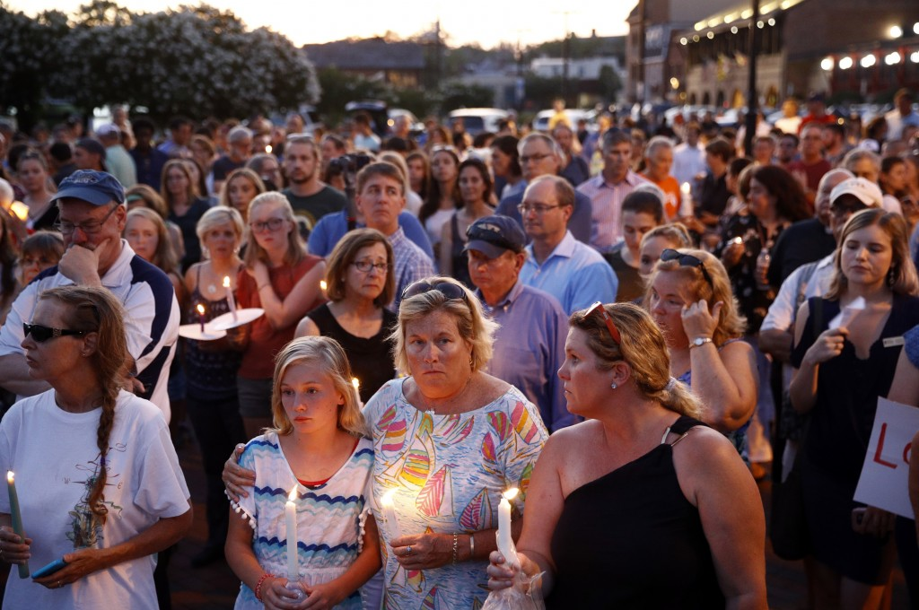 FILE - In this June 29, 2018, file photo, mourners stand in silence during a vigil in response to a shooting at the Capital Gazette newsroom, in Annap...