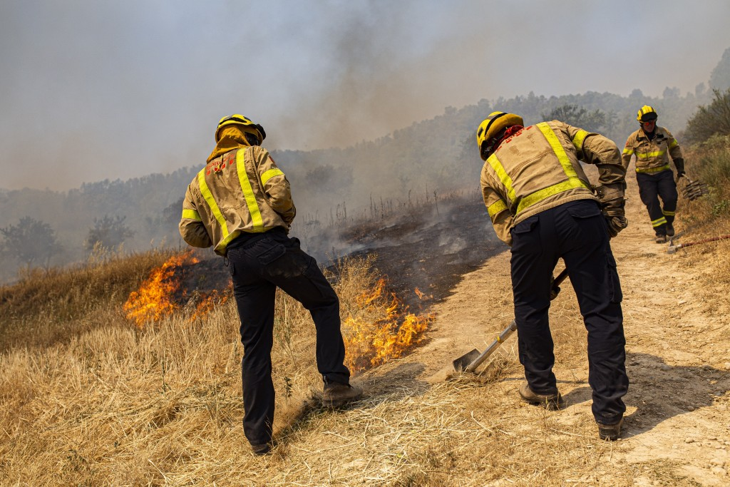 Firefighters try to extinguish a wildfire in Palma d'Ebre, near Tarragona, Spain, Thursday, June 27, 2019. Authorities suspect the cause of the outbre...