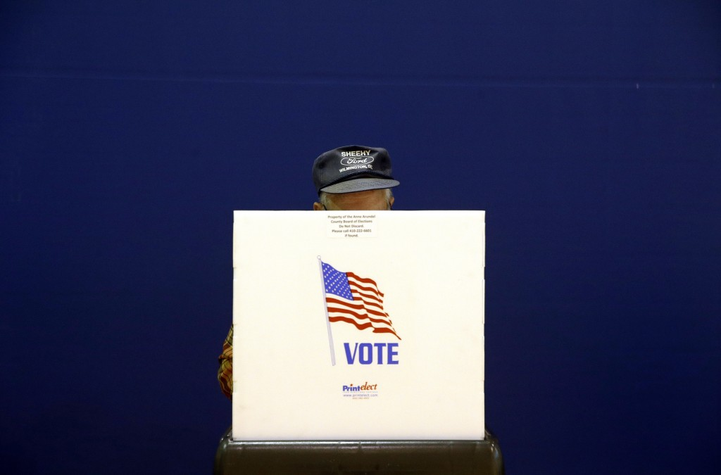 FILE - In this Nov. 6, 2018 file photo, a voter fills out a ballot at a polling place at Lake Shore Elementary School, in Pasadena, Md. A new survey f...