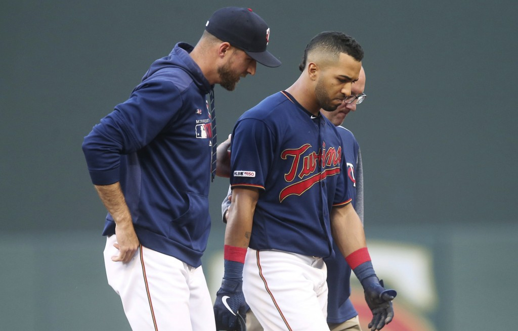Minnesota Twins' Eddie Rosario, center, is helped off the field by manager Rocco Baldelli, left, and trainer Tony Leo following an injury after he rou...