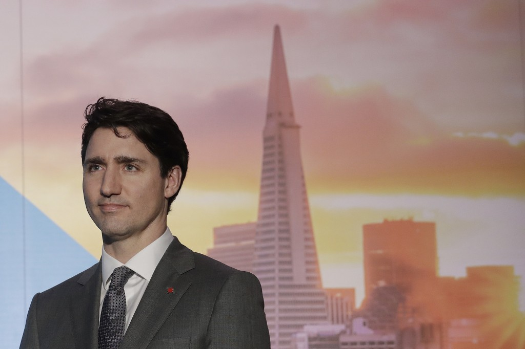 FILE - In this Feb. 8, 2018, photo, with an image of the San Fransisco skyline in the background, Canada's Prime Minister Justin Trudeau waits to spea...