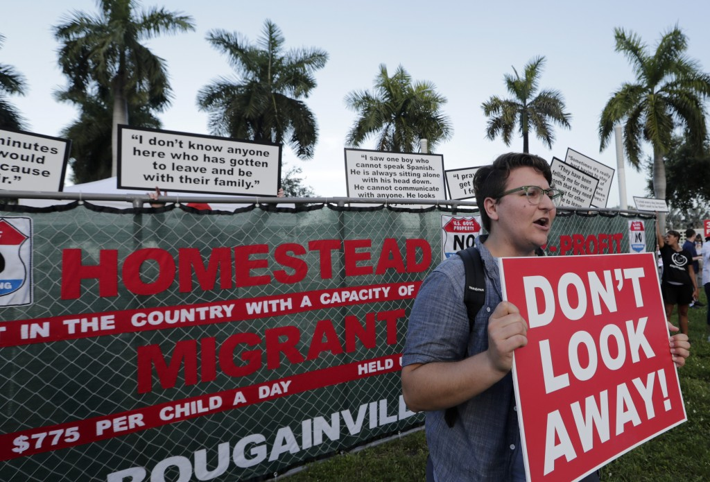 Kody Hersh holds a sign in front of a mock fence representing the Homestead Temporary Shelter for Unaccompanied Children, during a protest against the...