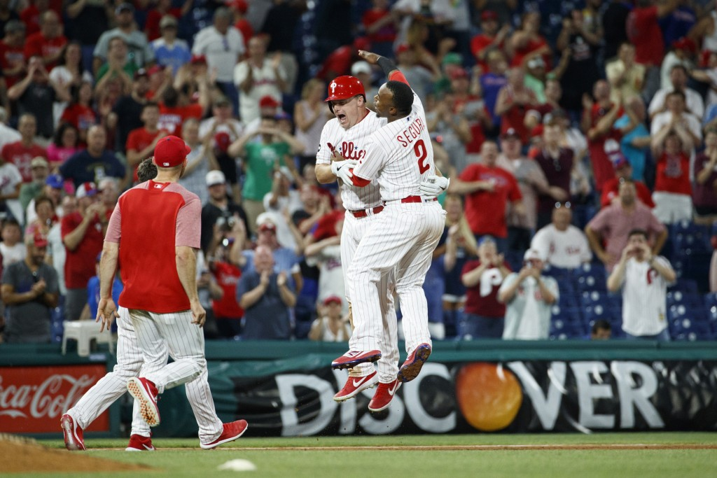 Philadelphia Phillies' Jay Bruce, left, and Jean Segura celebrate after Bruce drove in the winning run with a double off New York Mets relief pitcher ...
