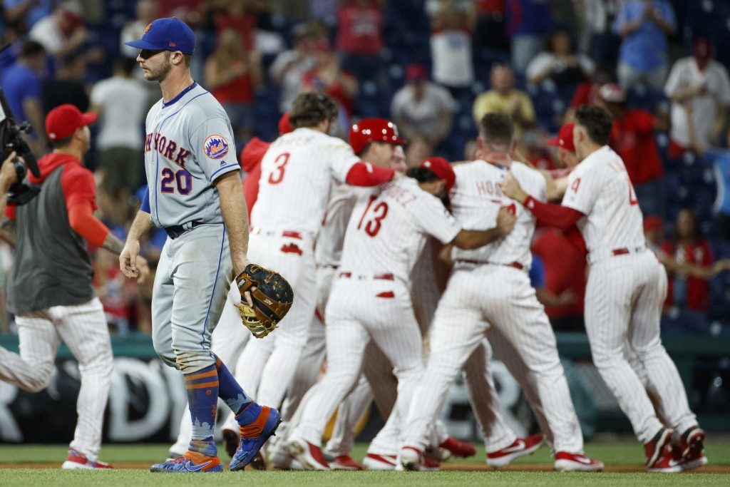 New York Mets first baseman Pete Alonso, left, walks off the field as the Philadelphia Phillies celebrate a double by Jay Bruce that drove in the winn...