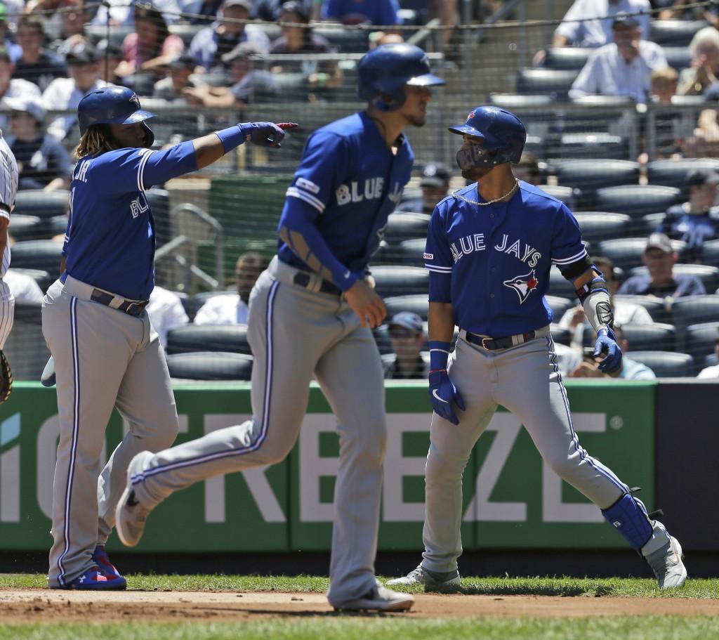 Toronto Blue Jays' Lourdes Gurriel Jr., right, celebrates his three-run home run with Cavan Biggio, center, and Vladimir Guerrero Jr. during the first...
