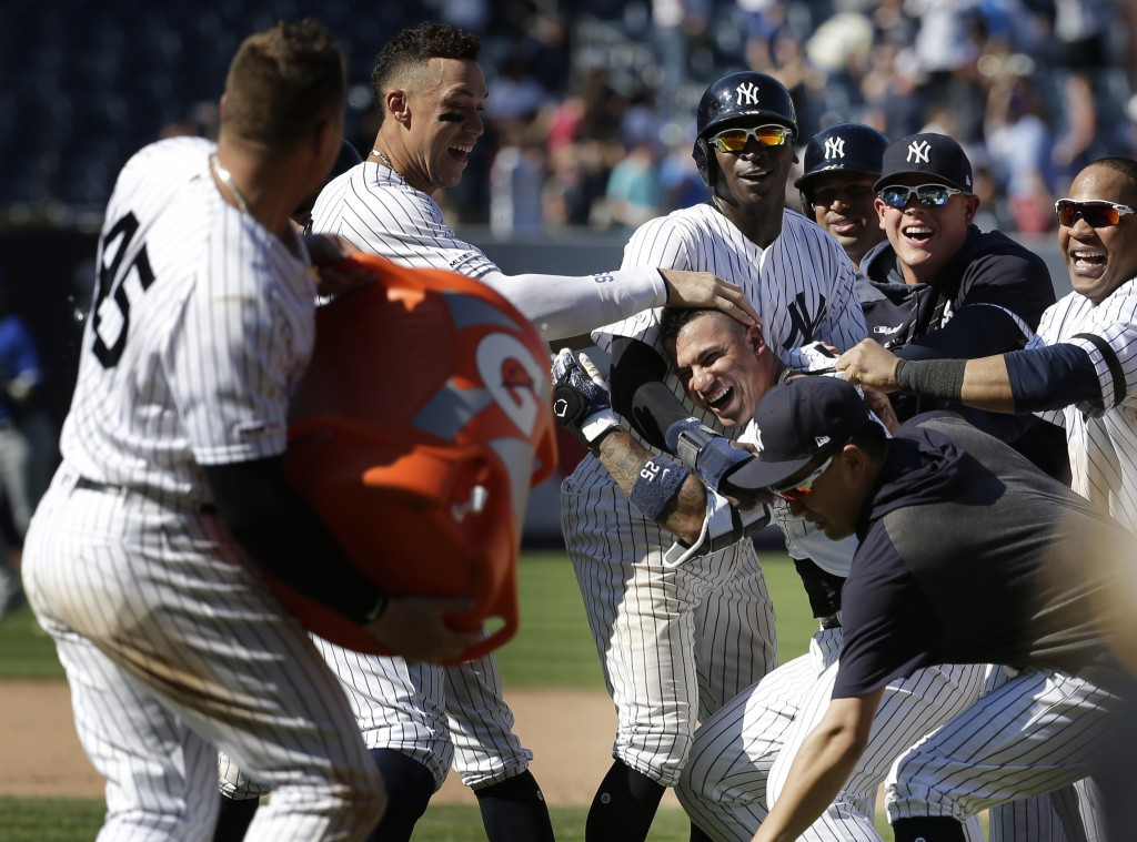 New York Yankees' Gleyber Torres, center right, celebrates his walk-off RBI single with teammates after the baseball game against the Toronto Blue Jay...