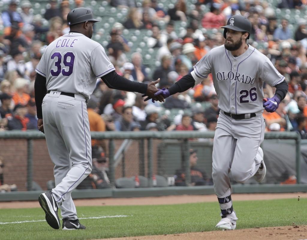Colorado Rockies' David Dahl, right, is congratulated by third base coach Stu Cole (39) after hitting a grand slam off San Francisco Giants' Jeff Sama...