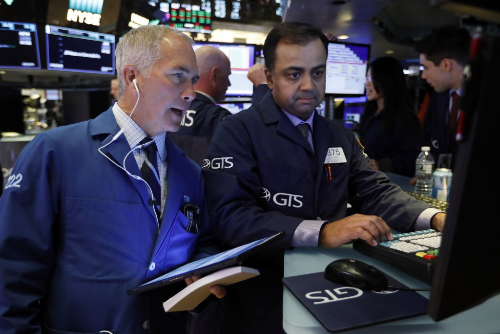 FILE - In this June 11, 2019, file photo trader Timothy Nick, left, and specialist Dilip Patel work on the floor of the New York Stock Exchange. The U...