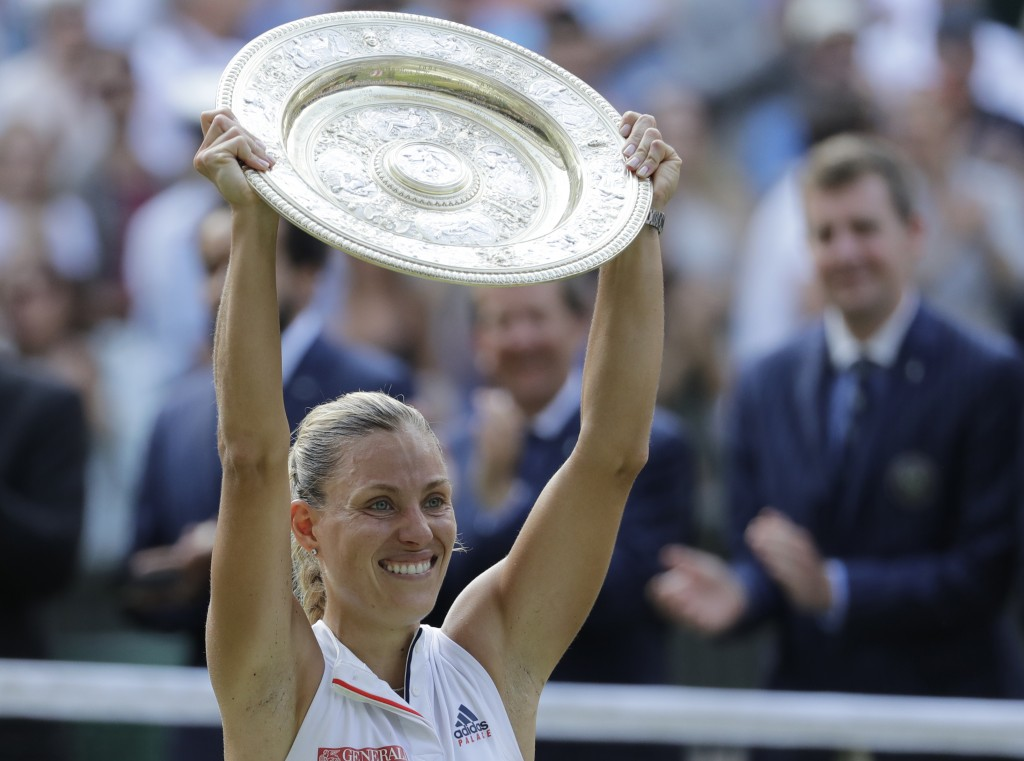 FILE - In this July 14, 2018, file photo, Germany's Angelique Kerber lifts the trophy after winning the women's singles final match against Serena Wil...
