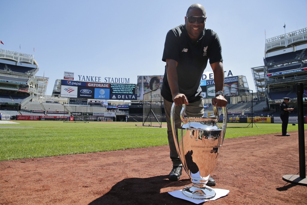 Former Liverpool FC player John Barnes poses for a picture with a replica of the Champions League trophy before a baseball game at Yankee Stadium, Wed...