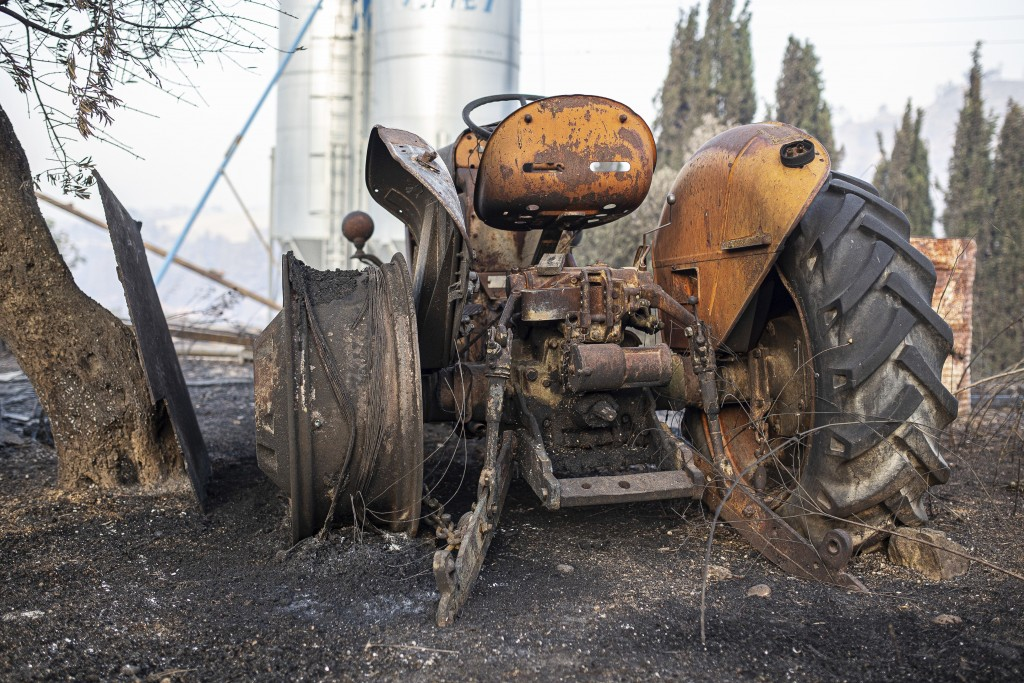A burned farm tractor lays destroyed after a wildfire swept through Torre de l'Espanyol, near Tarragona, Spain, Thursday, June 27, 2019.  The Cataloni...