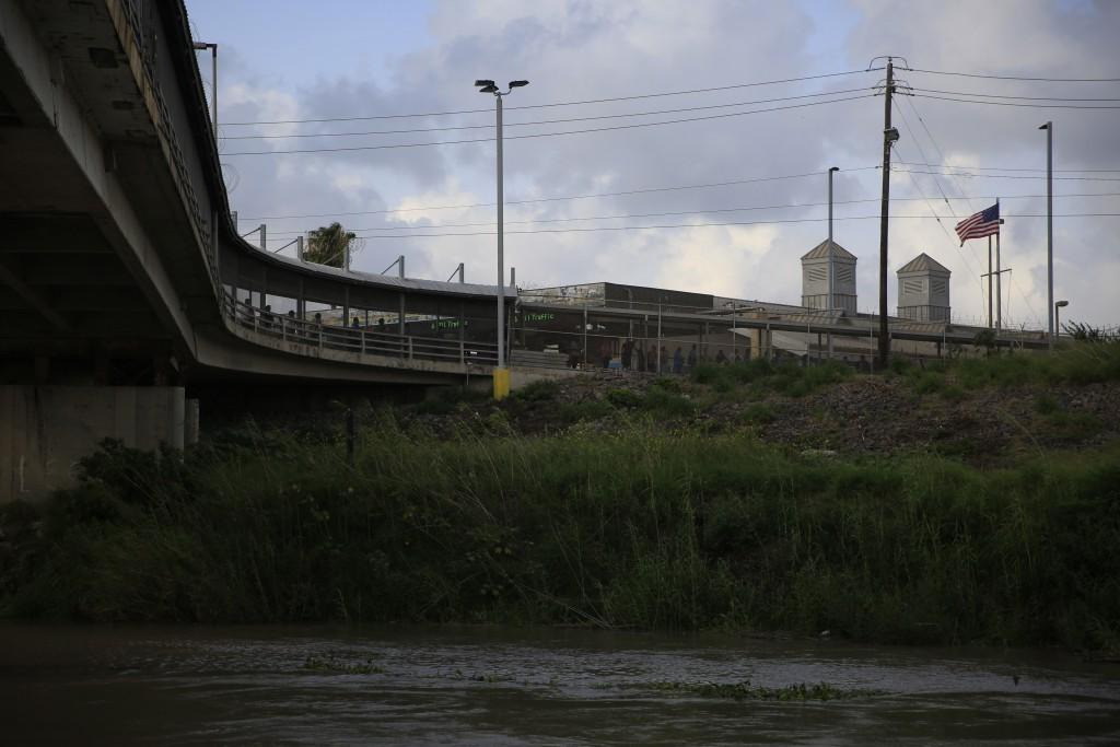 Pedestrian commuters wait in line to enter Brownsville, Texas, on the Puerta Mexico bridge across the Rio Grande, seen from downtown Matamoros, Tamaul...