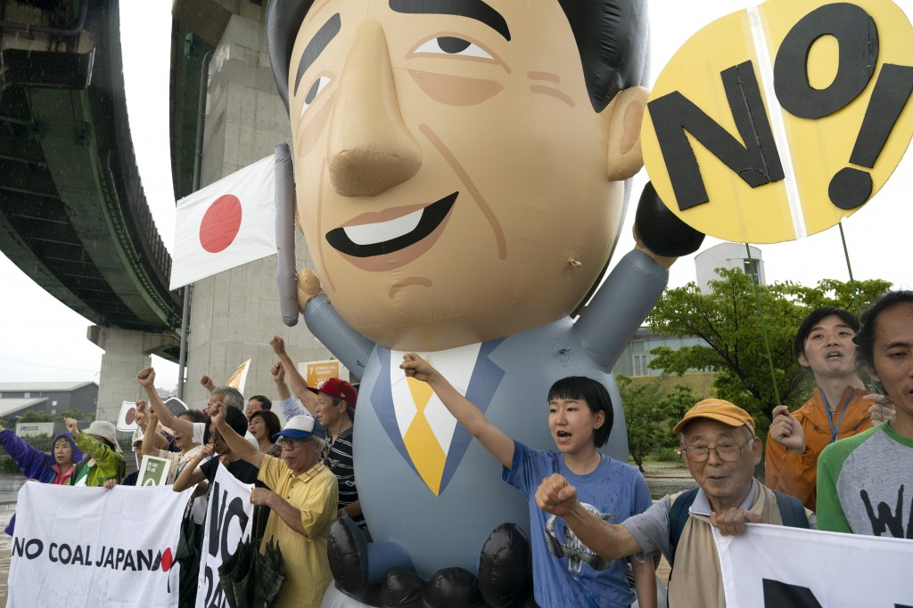 Environmental activists and local residents chant slogans as they stand next to an inflatable depicting Japanese Prime Minister Shinzo Abe during a pr...