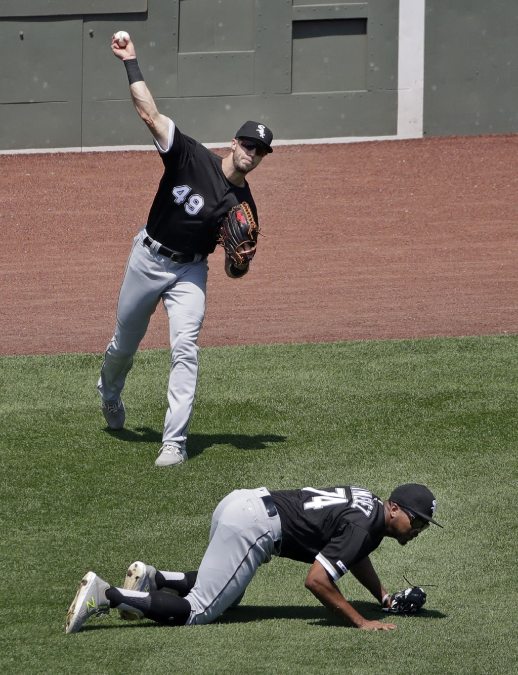 Chicago White Sox left fielder Eloy Jimenez (74) ducks down so center fielder Ryan Cordell (49) has a clear throw into the infield after a single by B...
