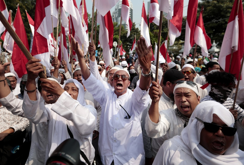 In this Thursday, June 27, 2019, file photo, supporters of Indonesian presidential candidate Prabowo Subianto shout slogans during a rally near the Co...