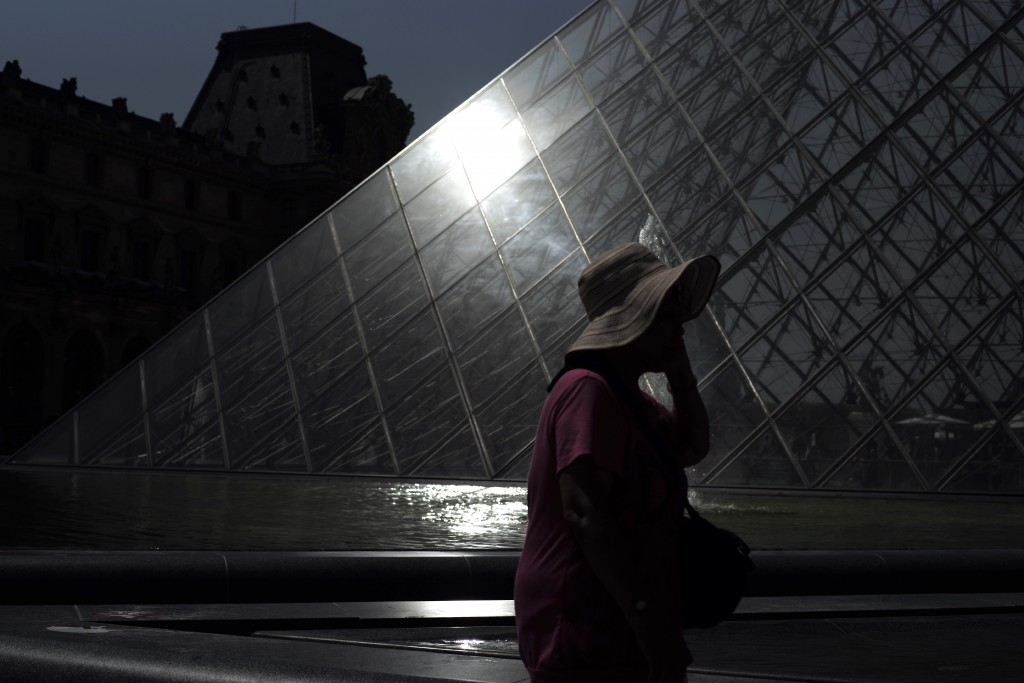 A woman wears a hat to protect from the sun as she walks past the Louvre museum Thursday, June 27, 2019 in Paris. Around France, some schools are clos...