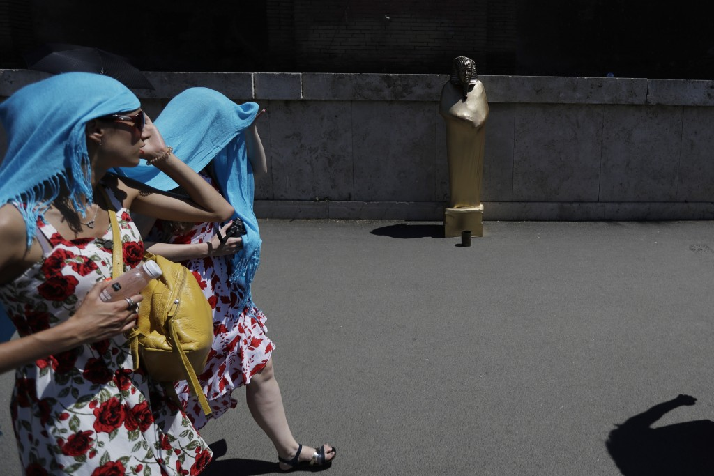 Tourists wear a scarf over their head to protect themselves from the sun as they walk past a street performer impersonating an Egyptian sphinx, in Rom...