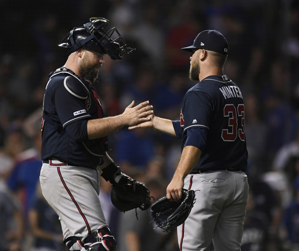 Atlanta Braves closing pitcher A.J. Minter right, celebrates with catcher Brian McCann after the Braves defeated the Chicago Cubs 5-3 in baseball game...