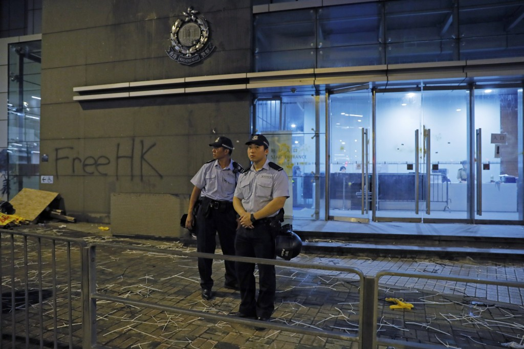 Riot police stand guard at a entrance after they clear barricades blocked by protesters outside the police headquarters as thousands gathered to deman...