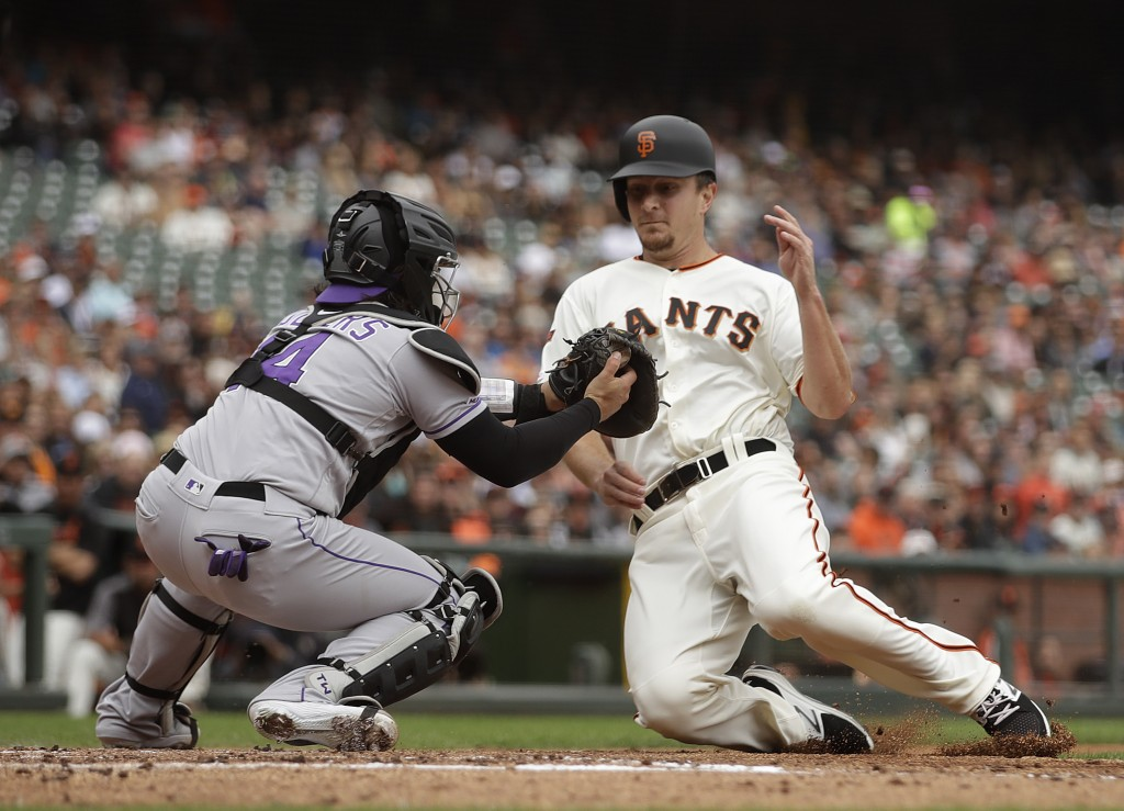 Colorado Rockies catcher Tony Wolters, left, tags out San Francisco Giants' Alex Dickerson in the first inning of a baseball game Wednesday, June 26, ...