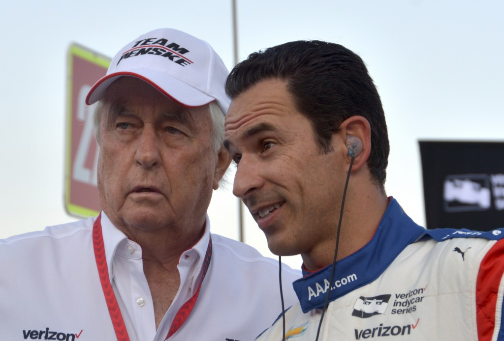 FILE - In this June 10, 2017, file photo, team owner Roger Penske, left, talks with driver Helio Castroneves, of Brazil, on pit road before an IndyCar...