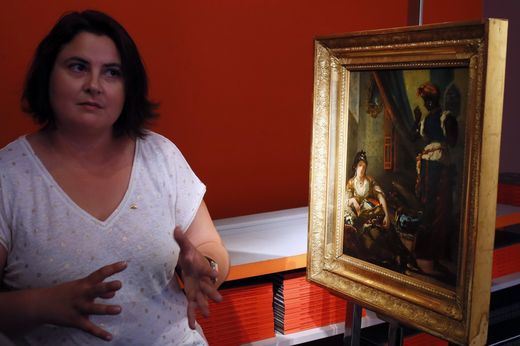 "Virginie Cauchi-Fatiga, a Delacroix expert, speaks during an interview about the oil painting ""Women of Algiers in their Apartment"" in Paris, Friday, ..."
