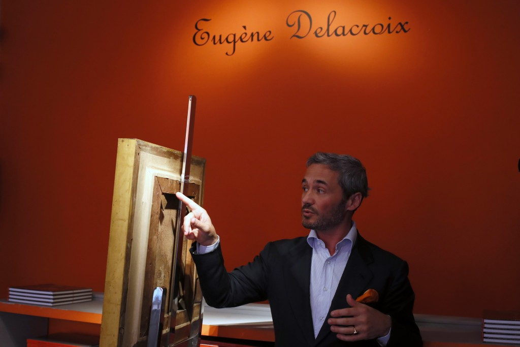 In this photo taken on Friday, June 21, 2019 Philippe Mendes, owner of the Galerie Mendes shows a detail at the back of Eugene Delacroix's oil paintin...