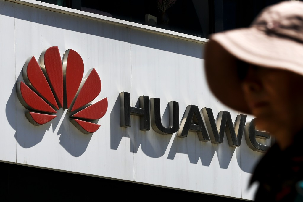 FILE - In this May 29, 2019, file photo, a woman walks by a Huawei retail store in Beijing. A federal jury in Texas rejected Wednesday, June 26, 2019,...
