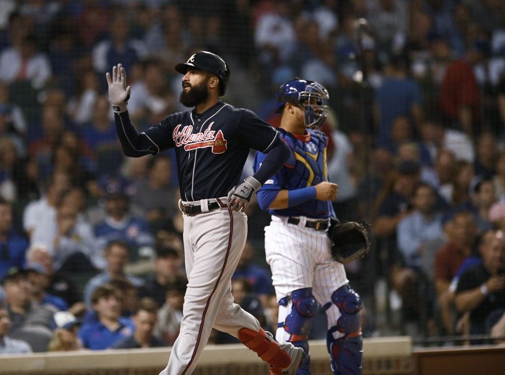 Atlanta Braves' Nick Markakis left, celebrates at home plate after hitting a three-run home run while Chicago Cubs catcher Willson Contreras right, wa...