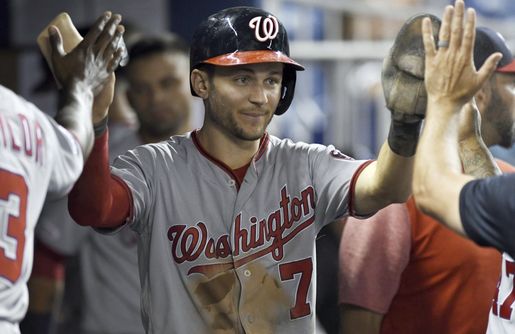 Washington Nationals' Trea Turner is congratulated by teammates after scoring against the Miami Marlins during the ninth inning of a baseball game Wed...
