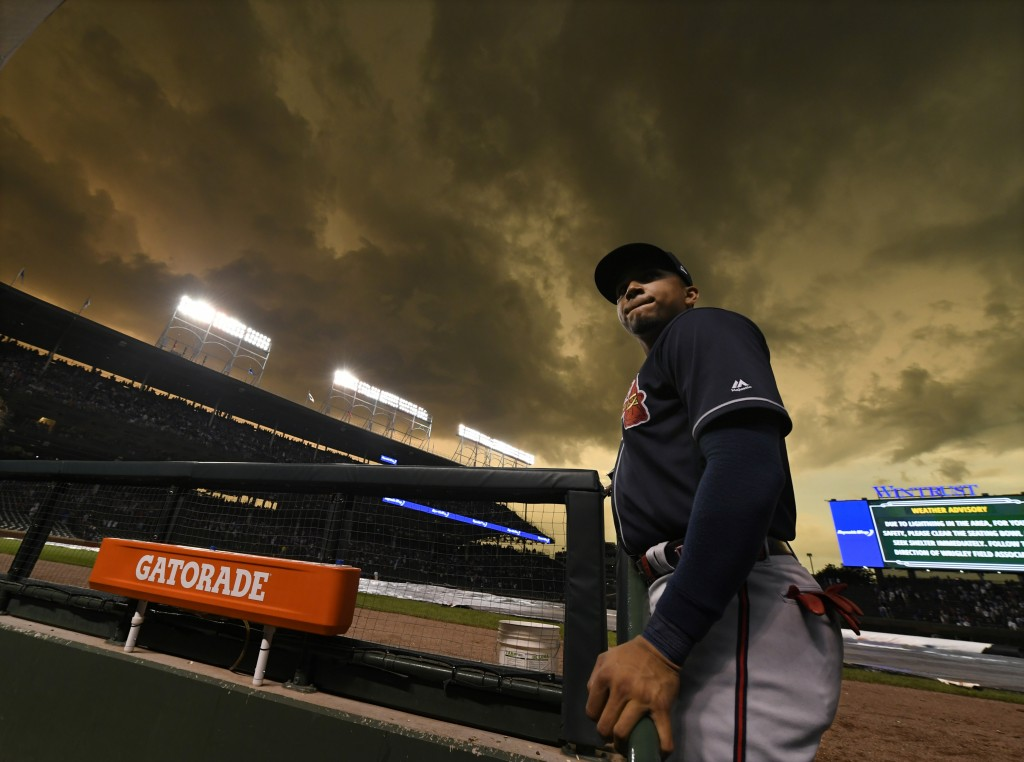 Atlanta Braves left fielder Johan Camargo looks out from the dugout during a lightning delay in the fourth inning of the team's baseball game against ...