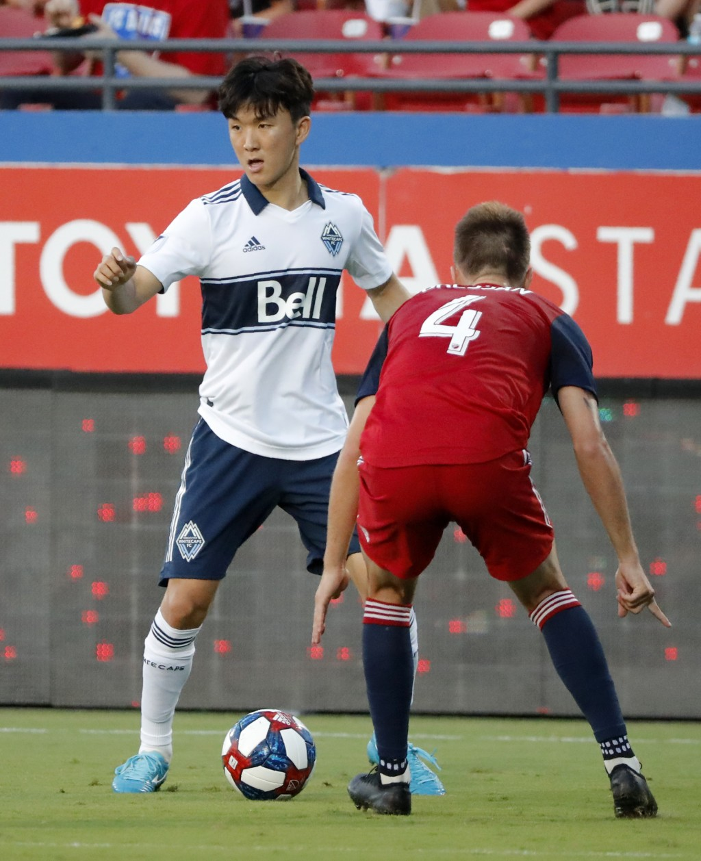 Vancouver Whitecaps's Inbeom Hwang (4) works to make a pass as FC Dallas' Bressan (4) defends during the first half of an MLS soccer match in Frisco, ...