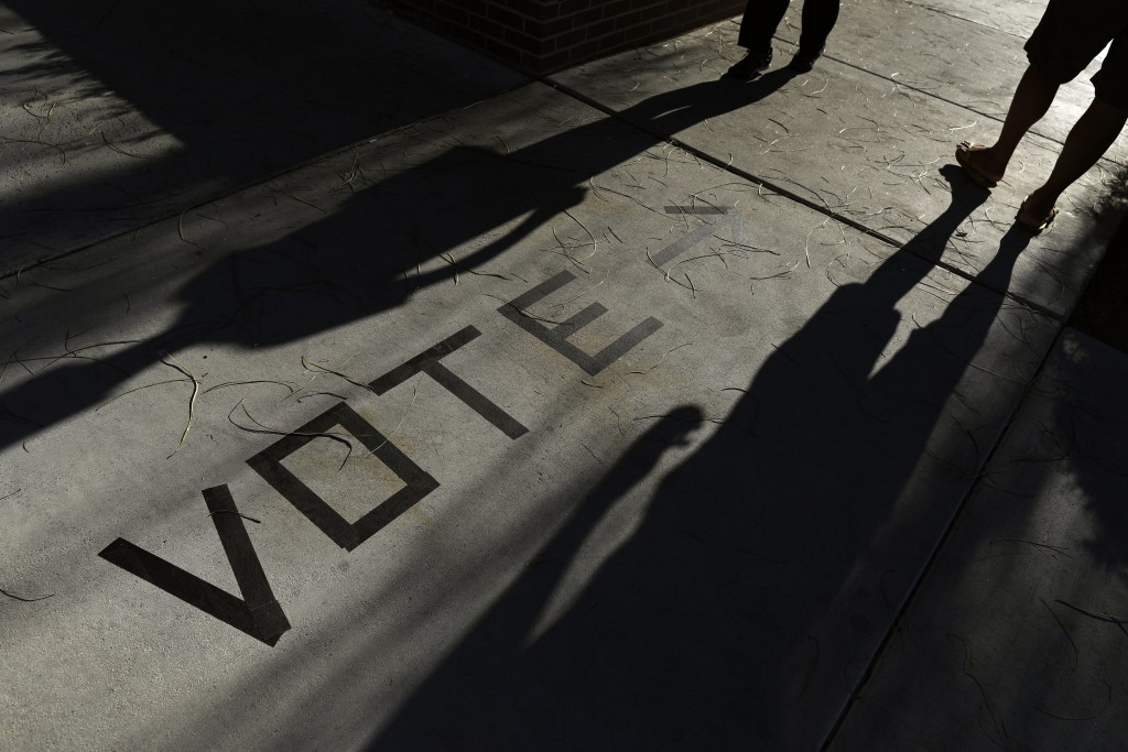 FILE - In this Nov. 6, 2018 file photo, voters head to the polls at the Enterprise Library,  in Las Vegas. A new survey finds that more than 120 milli...