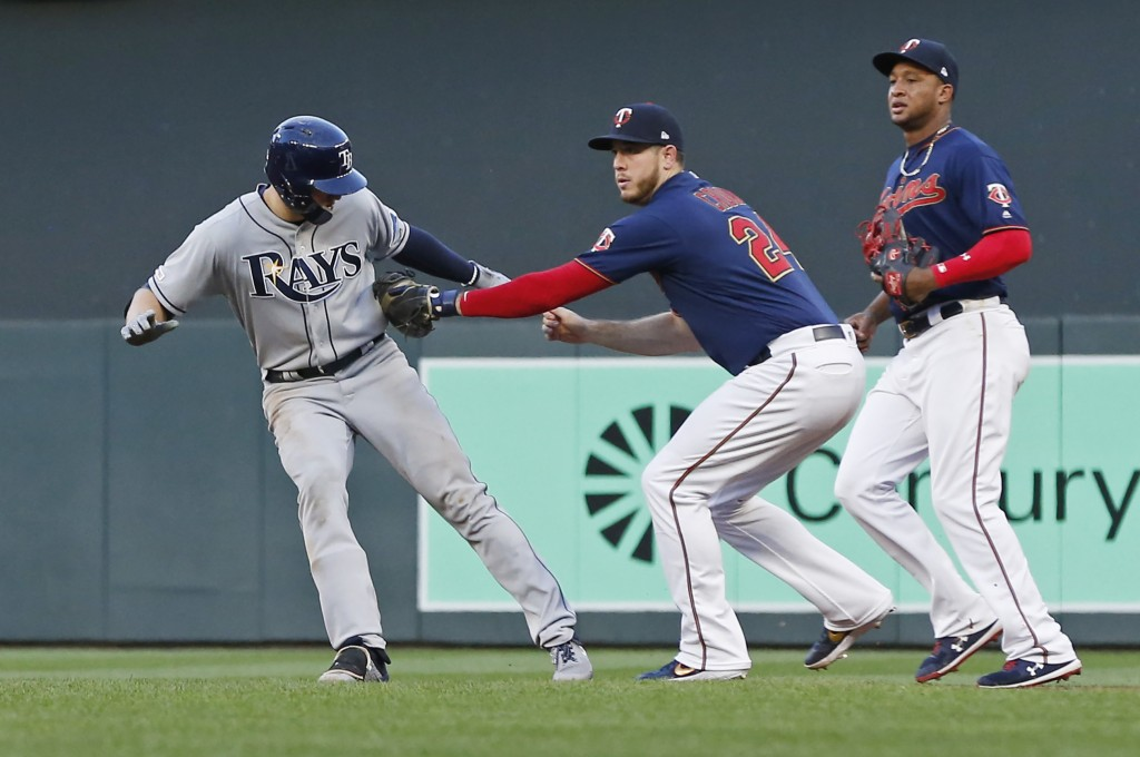 Tampa Bay Rays' Austin Meadows, left, is tagged out in a rundown by Minnesota Twins first baseman C.J. Cron during the fourth inning of a baseball gam...