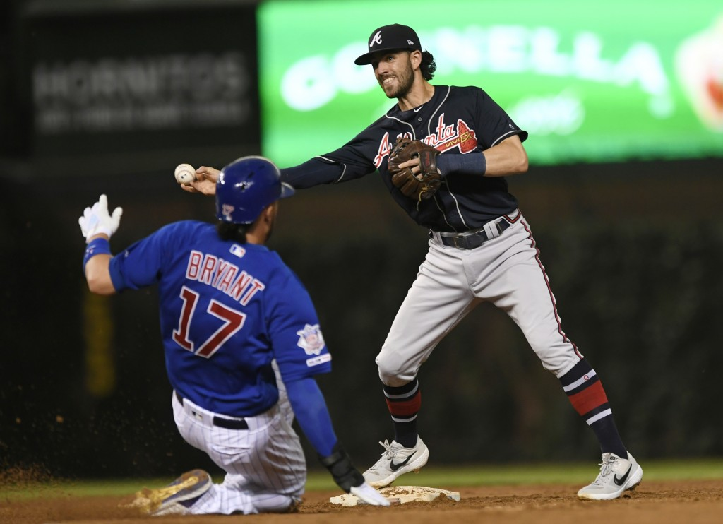 Atlanta Braves shortstop Dansby Swanson right, throws to first base after forcing out Chicago Cubs' Kris Bryant (17) at second base, on a double play ...