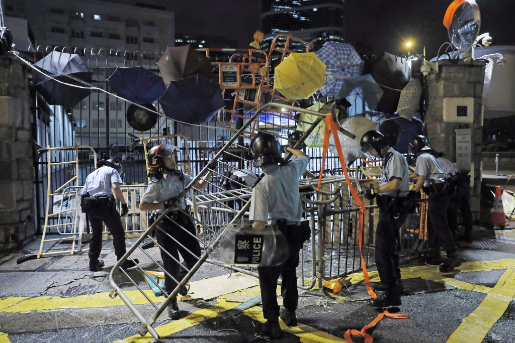 Riot police clear barricades blocked by protesters outside the police headquarters as thousands gathered to demand for an independent inquiry into a h...