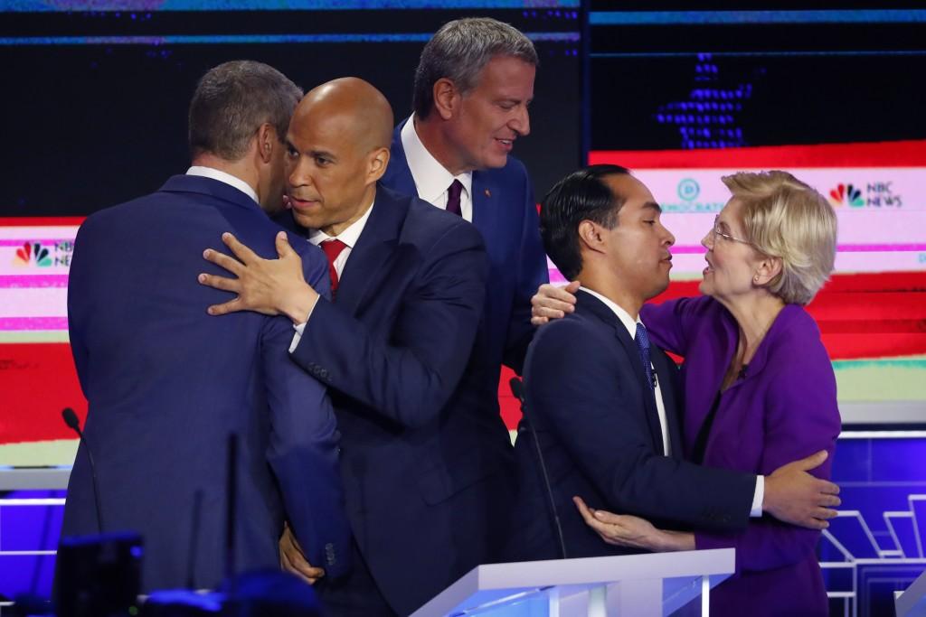Democratic presidential candidate Sen. Cory Booker, D-N.J., second from left, hugs Rep. Tim Ryan, D-Ohio, while Sen. Elizabeth Warren, D-Mass., hugs f...