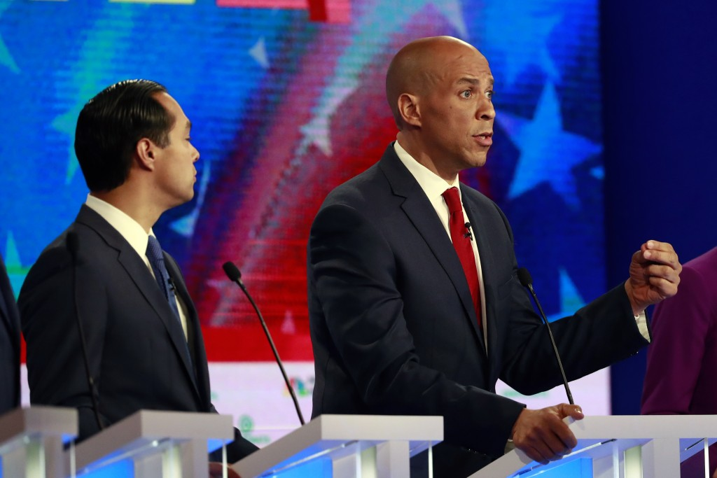 Democratic presidential candidate Sen. Cory Booker, D-N.J., gestures as former Housing and Urban Development Secretary Julian Castro listens, during s...
