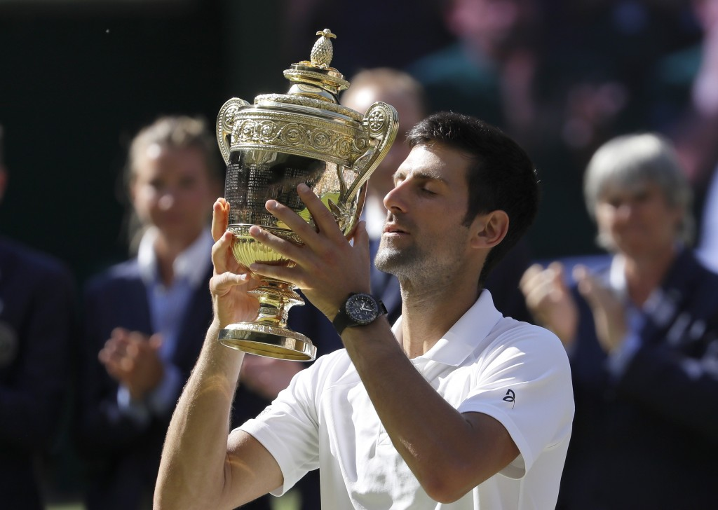 FILE - In this July 15, 2018, Serbia's Novak Djokovic lifts the trophy after winning the men's singles final against Kevin Anderson, of South Africa, ...
