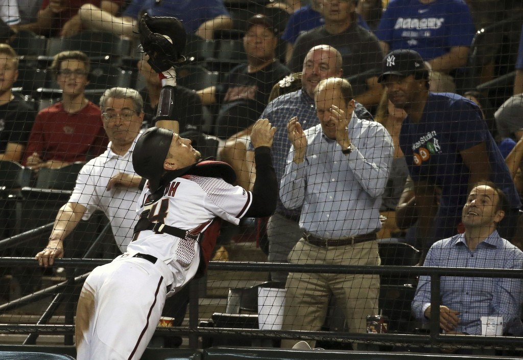 Arizona Diamondbacks catcher Caleb Joseph dives into the netting to make a catch on a foul ball hit by Los Angeles Dodgers' Enrique Hernandez during t...