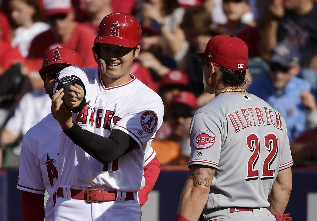Los Angeles Angels' Shohei Ohtani, left, of Japan, talks with Cincinnati Reds first baseman Derek Dietrich after hitting a single during the first inn...