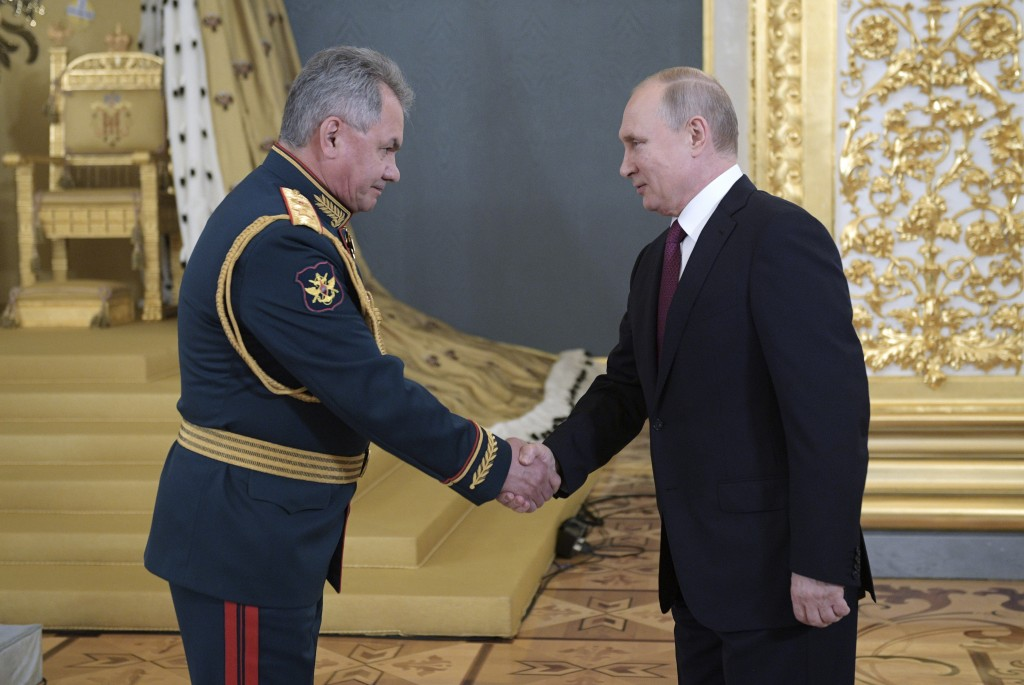 Russia's Defence Minister Sergei Shoigu, left, welcomes Russian President Vladimir Putin during a reception for graduates of Russian military educatio...