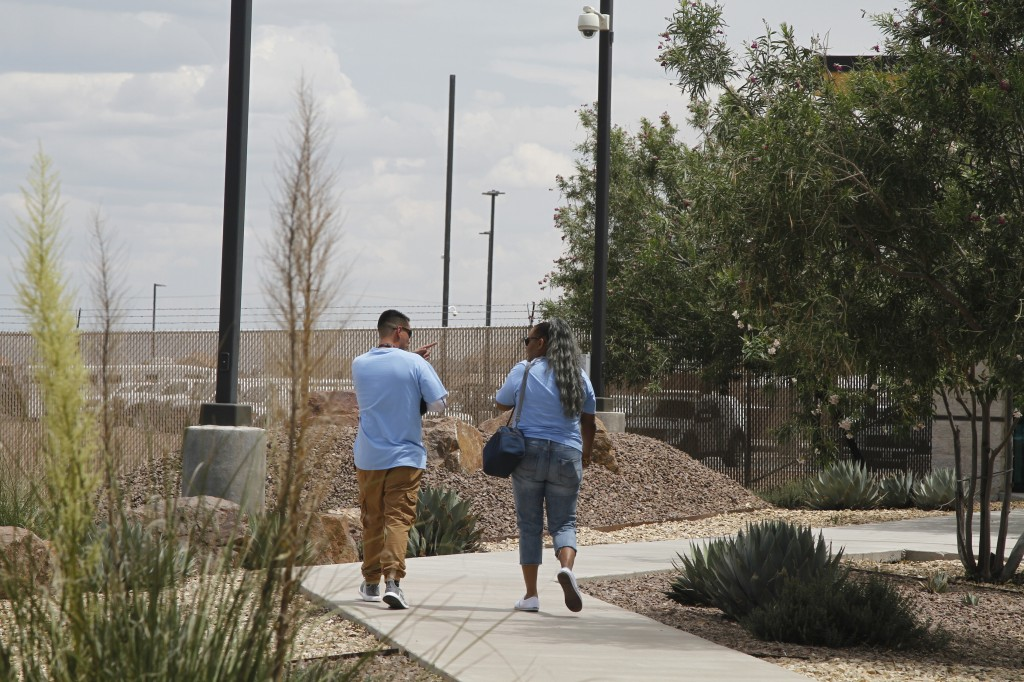"Two Border Patrol sub-contractors, ""monitors,"" brought for the first time to care for children walk outside at the Border Patrol station, Wednesday, J..."