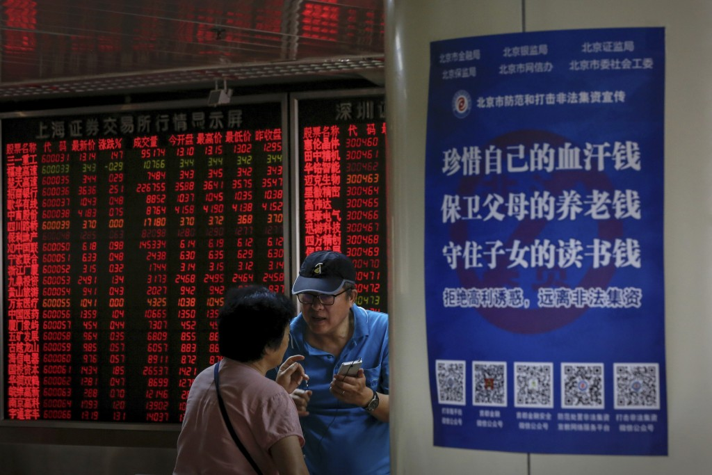 Chinese investors chat each other as they monitor stock prices at the brokerage house in Beijing, Thursday, June 27, 2019. Asian stocks advanced Thurs...