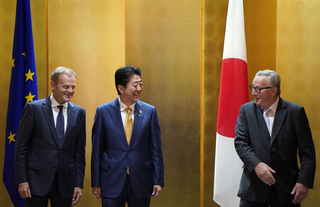 European Commission President Jean-Claude Juncker, right, and European Council President Donald Tusk, left, prepare for a photo with Japanese Prime Mi...