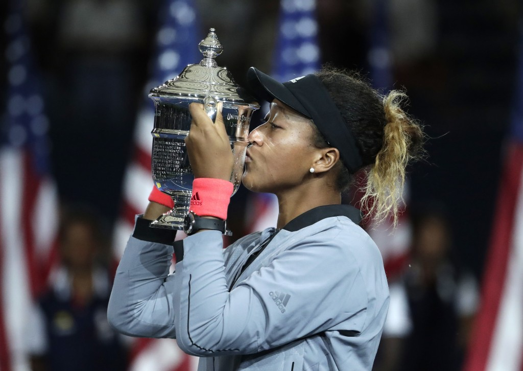 FILE - In this Sept. 8, 2018, file photo, Naomi Osaka, of Japan, kisses the trophy after defeating Serena Williams in the women's final of the U.S. Op...