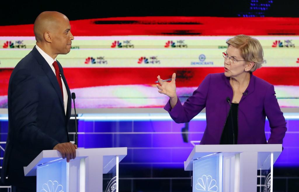Democratic presidential candidate Sen. Elizabeth Warren, D-Mass., gestures towards New Jersey Sen. Cory Booker, during a Democratic primary debate hos...