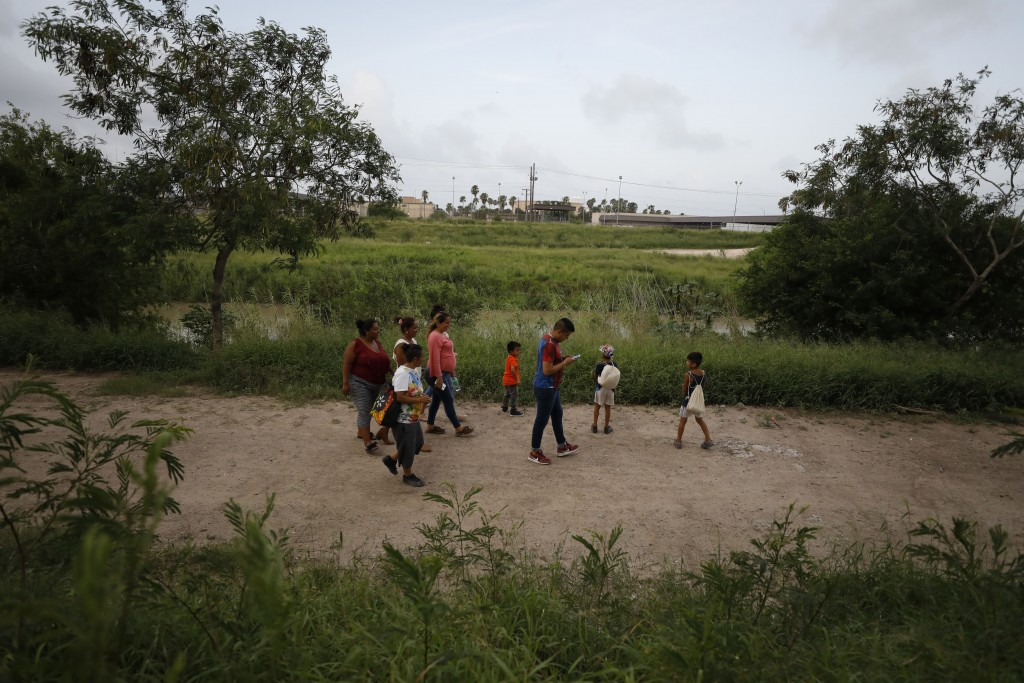 Migrants from Honduras, Nicaragua, and Mexico walk with two local friends along the Rio Grande, before they sleep for the night on the pavement at the...