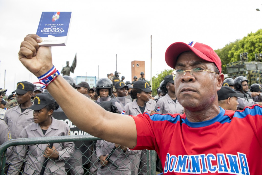 A man holds a copy of the Dominican Constitution during protests outside the National Congress, against a Constitutional reform that would allow Presi...