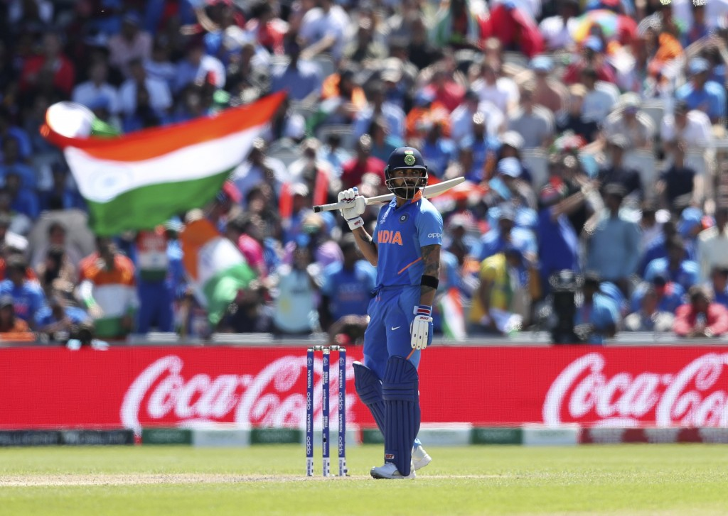 India's captain Virat Kohli follows the ball after playing a shot during the Cricket World Cup match between India and West Indies at Old Trafford in ...